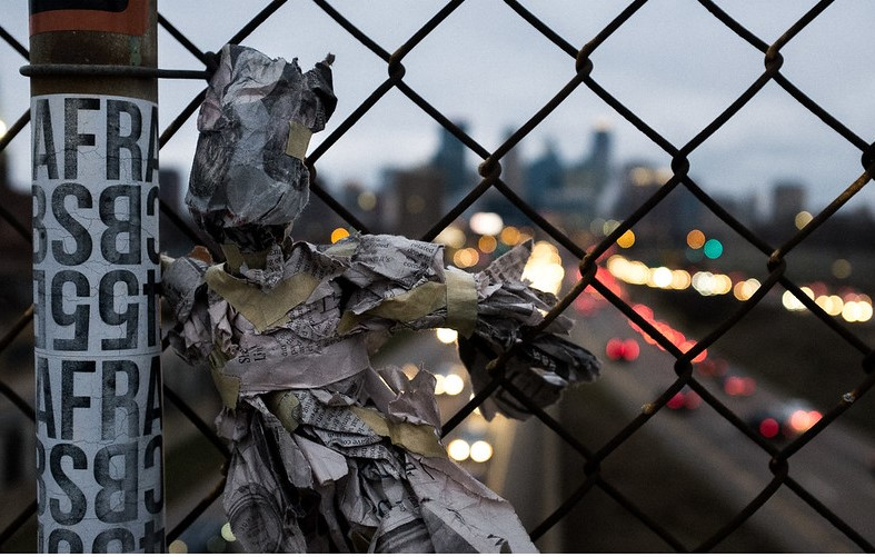 Image of newspaper puppet on chain link fence over highway bridge