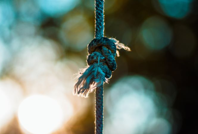 photo of vertical rope with frayed knot, blurred lighs in background