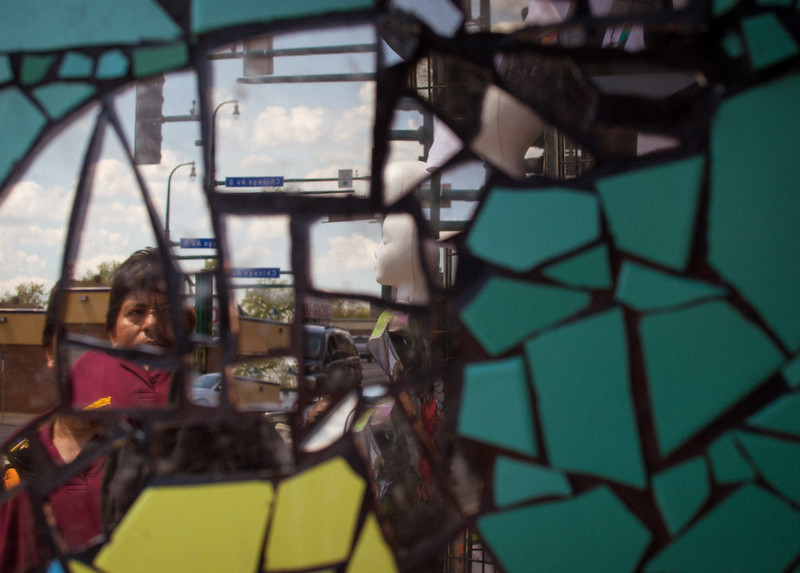 Mirror mosaic reflecting fractured images of man, car, and mannequin on street