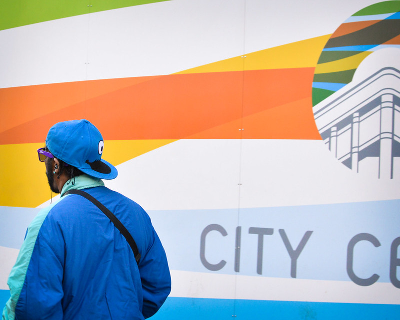 "A Black man with a backward ballcap and sunglasses walks away from us, past a wall with colored stripes and partial lettering ""City C..."""
