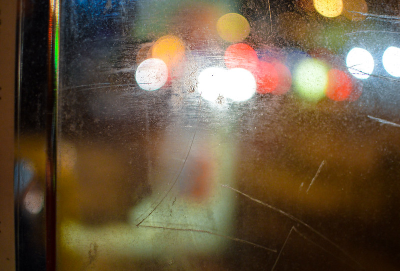 Image of scratched surface reflecting blurred, multicolored lights.