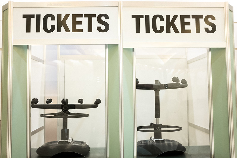 """Two booths marked """"TICKETS"""" with an office chair upside down on both counters"""