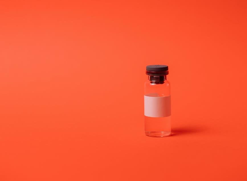 Glass vial on red-orange background